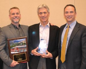 "Tim Oliver (center), flanked by two of his NexCore colleagues, Todd Varney (left) and Greg Venn (right), received his HREI Insights Awards™ Lifetime Achievement Award at the RealShare HRE conference in Scottsdale, Ariz., in December. NexCore also won the award in the ""Best New Development, MOBs and Other Outpatient Facilities (25,000 to 49,999 square feet)"" category. (HREI photo)"