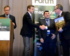 John B. Mugford, editor of Healthcare Real Estate Insights (far left), announces the 2018 HREI Insights Award for Best MOB of less than 25,000 square feet, which went to MedProperties Group. Accepting the award for MedProperties Group from HREI Publisher Murray W. Wolf (far right) during the awards presentation Dec. 6 were Dan Ahlering and Vlad Milrud.
